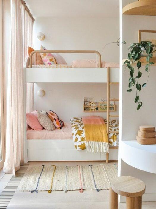 Habitación blanca con cama de dos pisos con mueble blanco y cobijas rosas