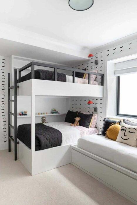 Habitación blanca con detalles negros en la pared con una cama de dos pisos con escaleras negras y cobijas blancas con negro