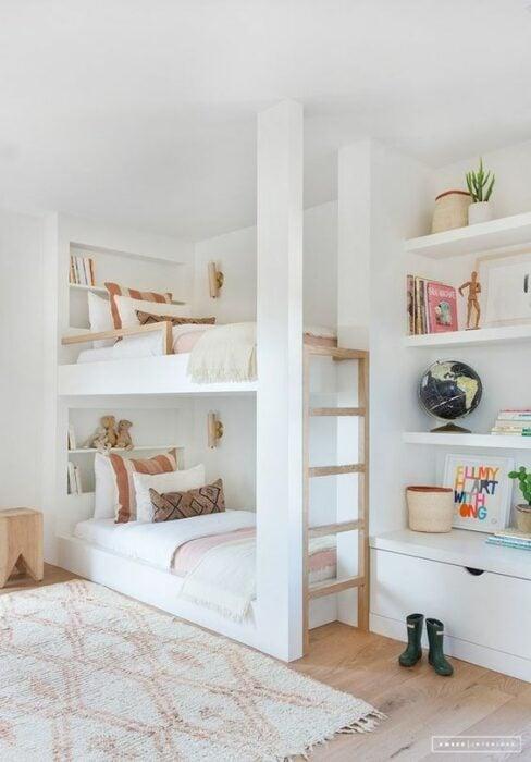 Habitación con paredes blancas, piso de madera y alfombra blanca con rombos rosas y una cama de dos pisos con cobijas blancas y cojines con figuras geométricas