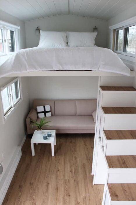 MIni casa con pisos de madera, paredes blanca con sillón rosa con mesita blanca y un cojin blanco en la parte de abajo y en la parte de arriba una cama matrimonial con cobijas blancas