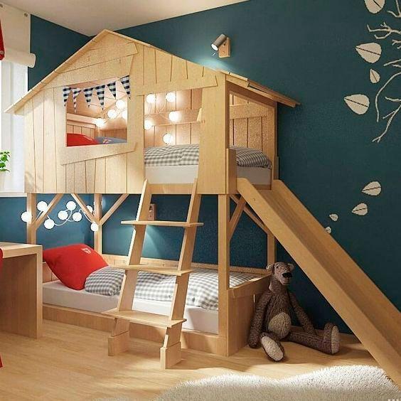Habitación con pared verde esmeralda y una mueble litera en forma de casita del árbol con camas con cobijas de cuadros grises