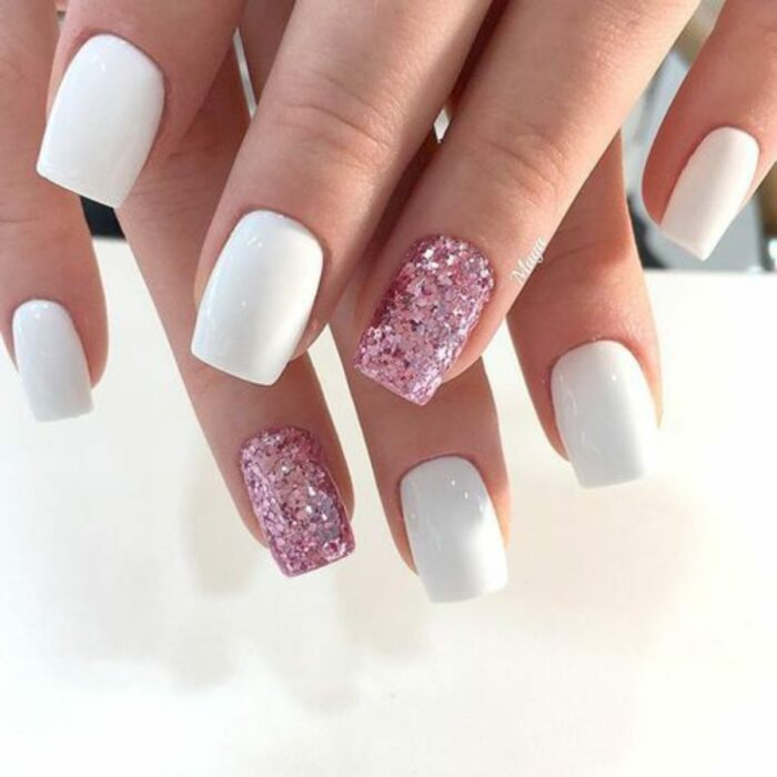 Chica con un diseño de uñas de color blanco con un toque de plateado y dorado