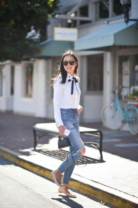 Slim girl with straight black medium hair wearing jeans torn from the knees, white shirt and black bow on the neck