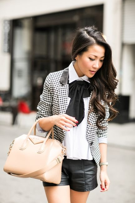 Asian girl with long, black and wavy hair holding a beige bag with right hand wearing a black leather shorts, white shirt, white jacket with black squares and a black bow at the neck