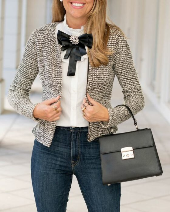 Blonde girl with loose wavy hair wearing dark jeans, white shirt and black bow on neck holding small square black bag with left arm
