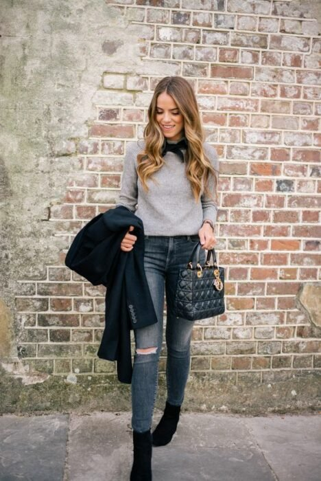 Wavy blonde hair girl looking down wearing knee ripped dark jeans with gray sweater and black bow on neck holding black jacket and bag in hands