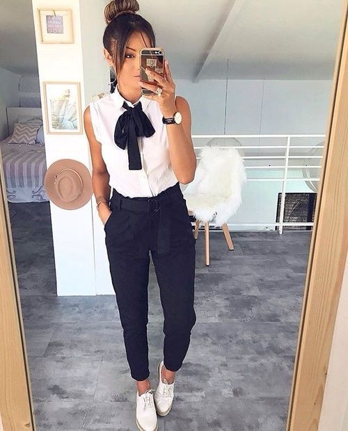 Girl taking a selfie in front of the mirror with dark pants, white sleeveless blouse and a black bow on the neck