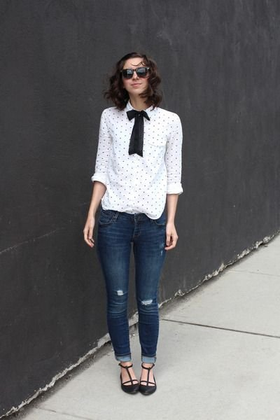 Slim girl in white blouse, dark jeans and black bow on the shirt