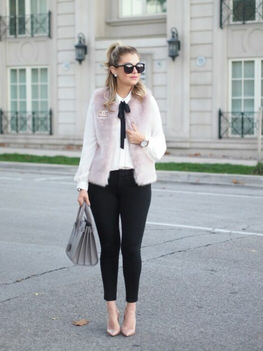 Blonde girl with half ponytail and sunglasses wearing black pants, white shirt, pink teddy coat with a black bow on the neck