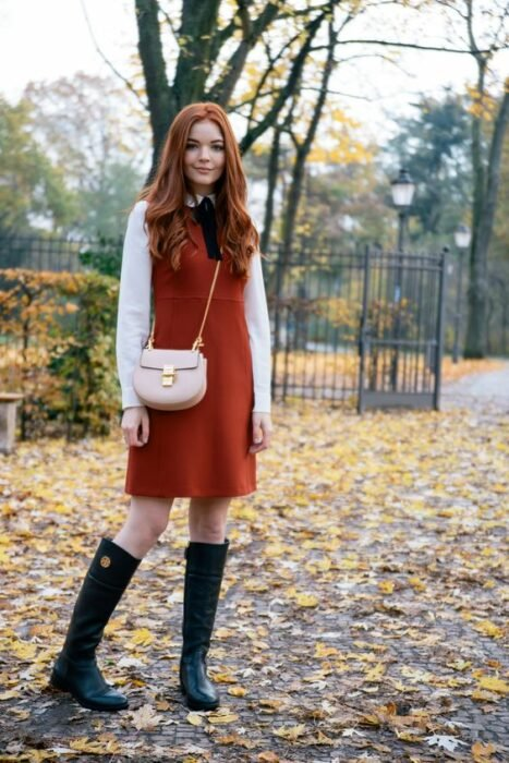 Red-haired girl with loose hair wearing a thick orange tank dress with a white blouse underneath with a black bow at the neck and black rain boots
