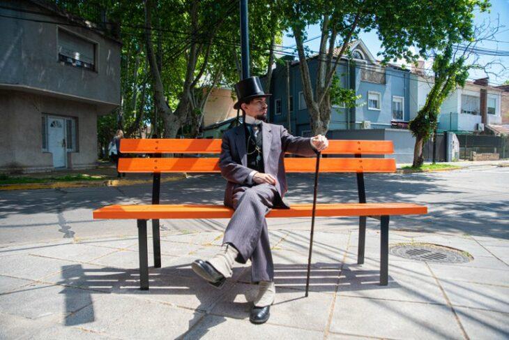 Santiago Pellegrini  sentado en una banca color naranja