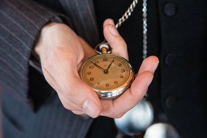 Mano sosteniendo un reloj de bolso dorado