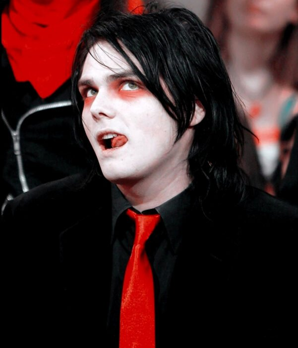 Gerard Way from My Chemical Romance, with long black hair, red eye shadows, black suit, red tie, pale skin