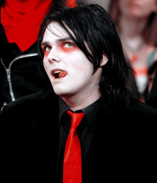 Gerard Way de My Chemical Romance, con cabello largo, negro, sombras de ojo rojas, traje negro, corbata roja, piel pálida