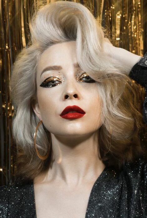 Chica con maquillae en dorado, delineado doble y labial rojo; Maquillajes para celebrar Navidad