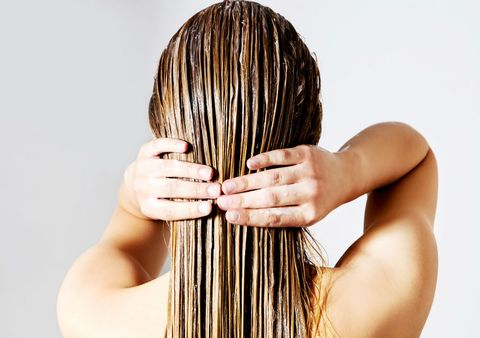 Blond woman from behind applying a mask on her hair