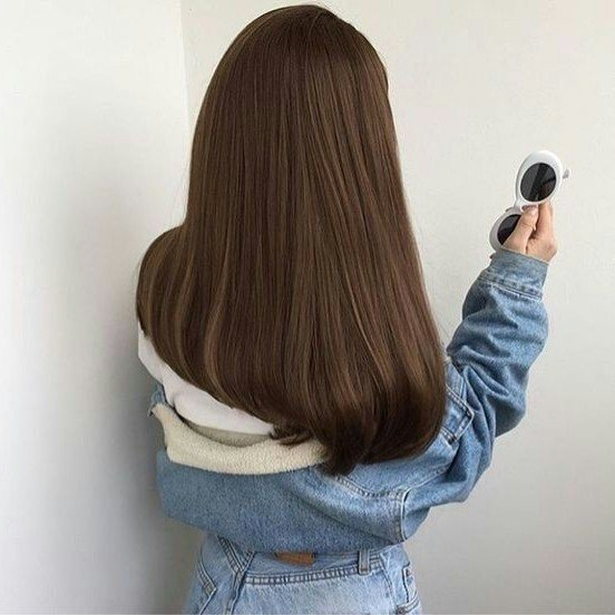 Girl from behind with long straight light hair wearing denim jacket