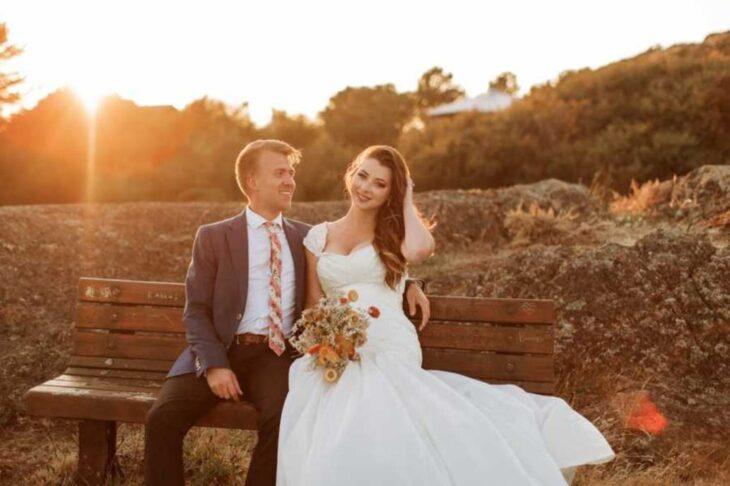 Lauren y Brayden Faganello en día de su boda sentados en una banca de madera en el atardecer
