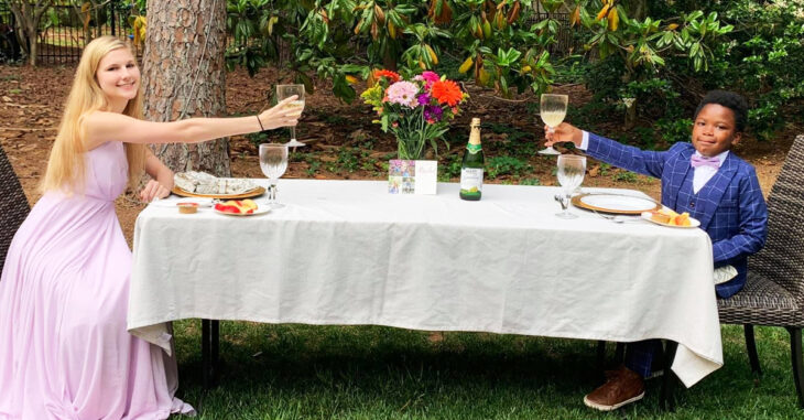 Niñera y niño teniendo una cena en el jardín