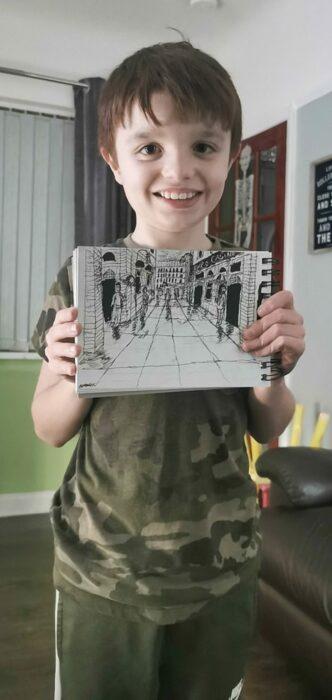 alex baker niño autista sosteniendo su libre de dibujo