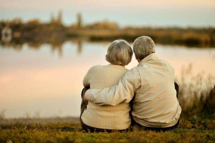 Pareja de ancianos sentados frente a un lago viendo el atardecer