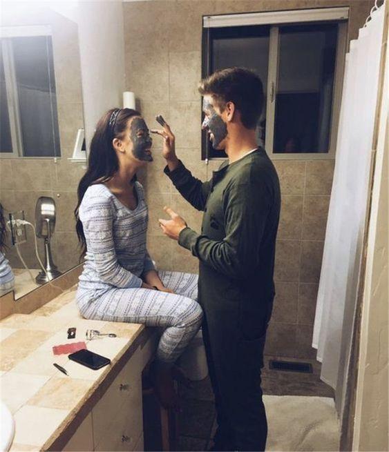 Chico poniendo una mascarilla a su novia mientras están en el cuarto de una habitación