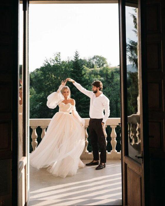 Pareja de novios el día de su boda bailando mientras están en una terraza