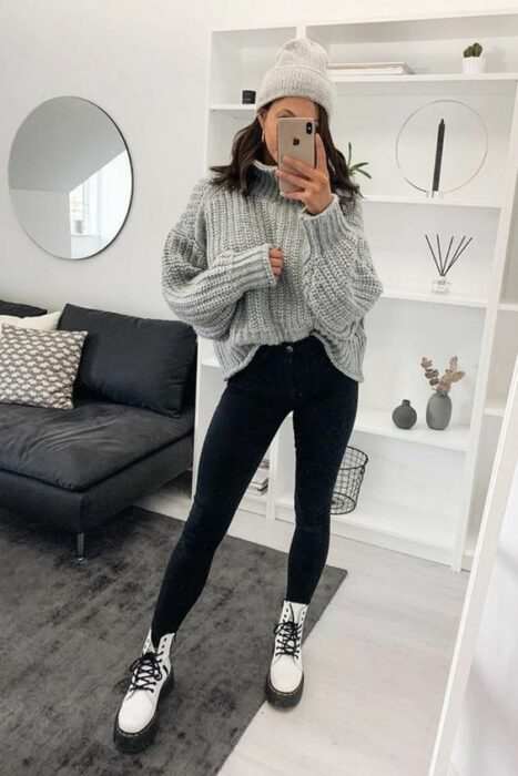 Girl wearing off-white beret, with oversized gray sweater, black jeans and white Dr. Martens style ankle boots