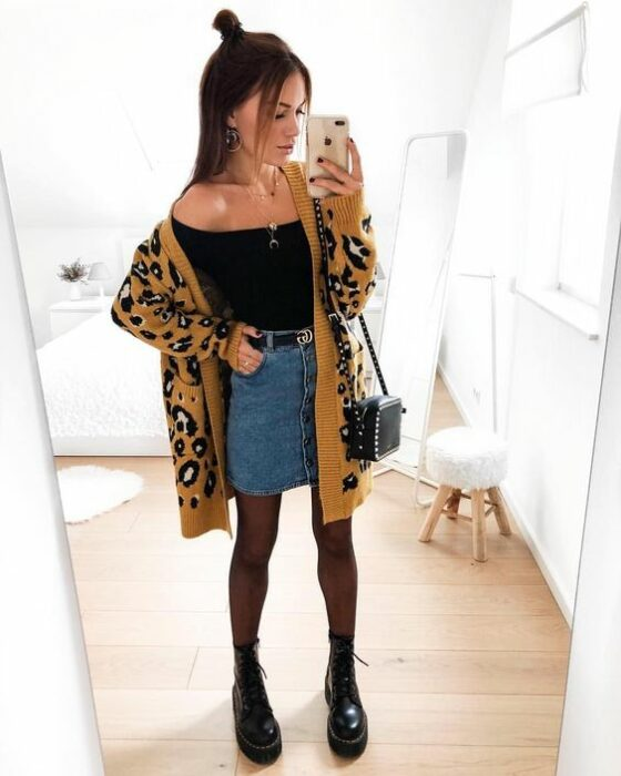 Girl wearing black blouse, denim mini skirt, with black tights and booties and a long animal print cardigan