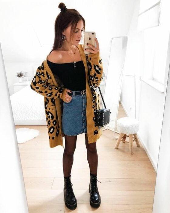 Chica usando blusa negro, mini falda denim, con medias y botines negros y un cardigan largo de estampado animal print