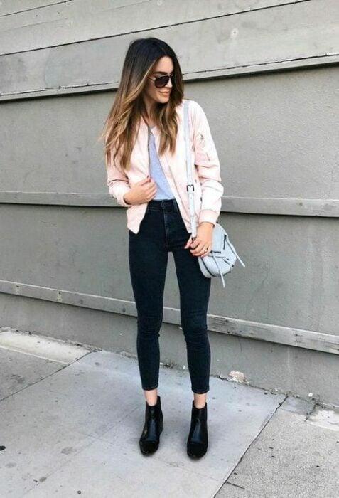 Chica usando gafas de sol, playera gris, chaqueta rosa bebé, jeans y botines color negro