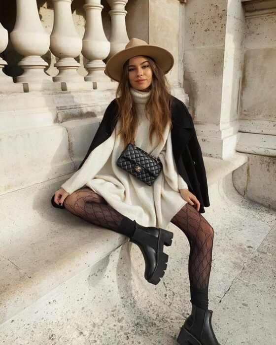 Girl wearing hat, black coat, white oversized cargidan style dress, with black stockings and ankle boots of the same color