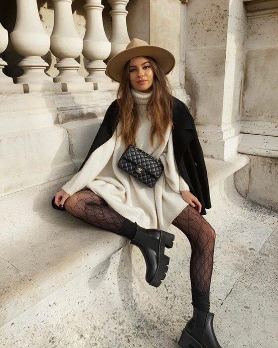 Chica usando sombrero, abrigo negro, vestido estilo cargidan oversized color blanco, con medias negras y botines del mismo color
