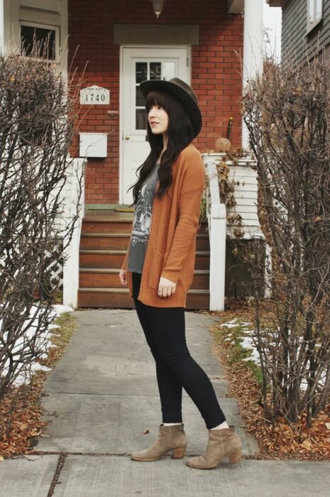 Girl wearing hat, gray blouse, burnt orange cardigan, black jeans and camel ankle boots