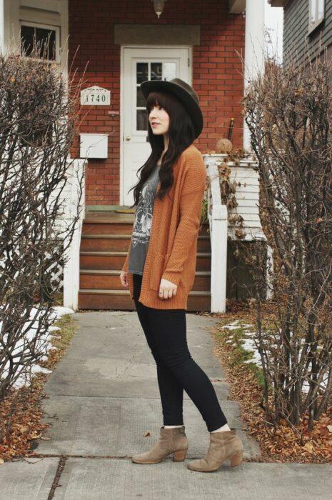 Chica usando sombrero, blusa gris, cardigan color naranja quemado, jeans negros y botines color camel
