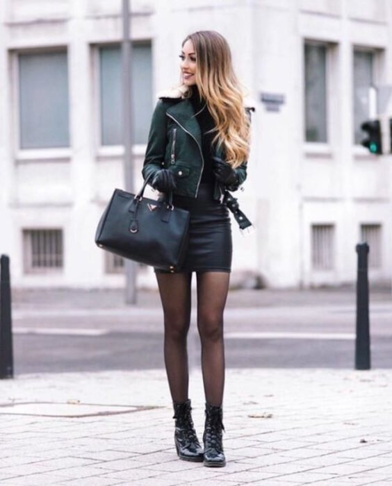 Girl wearing a total black look, sweater, mini skirt, leather jacket, handbag, stockings and ankle boots