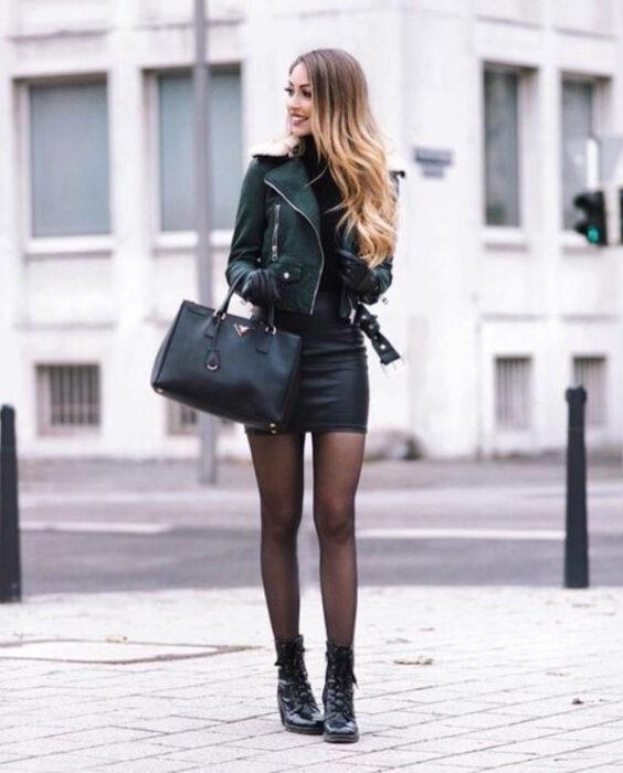 Chica usando un total black look, de suéter, mini falda, chaqueta de cuero, bolsa de mano, medias y botines