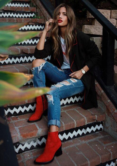 Chuica usando blazer negro, playera blanca, jeans rasgados y botines color rojo