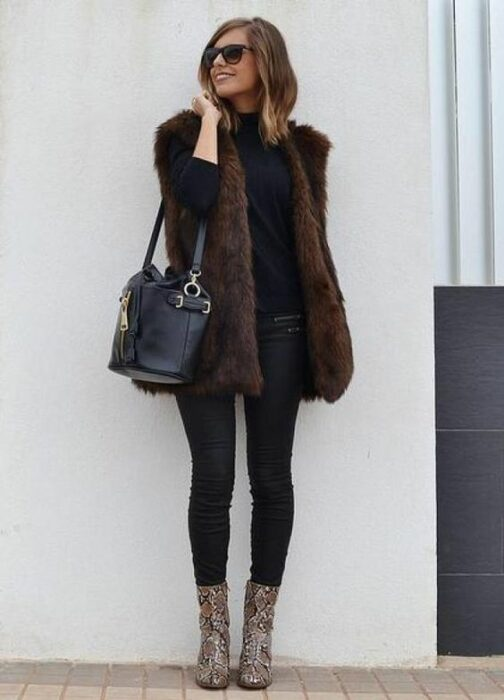 Girl wearing black sweater, jeans and handbag, with brown furry vest and vibora print ankle boots