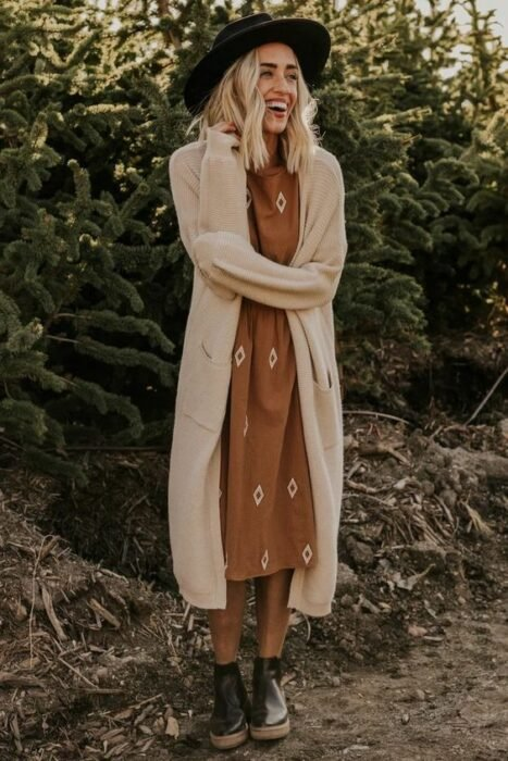 Girl wearing hat, mustard dress with long beige cardigan and black ankle boots