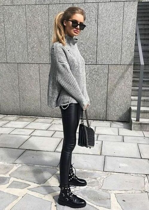 Girl wearing sunglasses, oversized sweater, vinyl leggings, black ankle boots and a black handbag