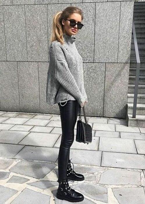 Chica usando lentes de sol, suéter oversized, leggings de vinipiel, botines negros y bolsa de mano negra