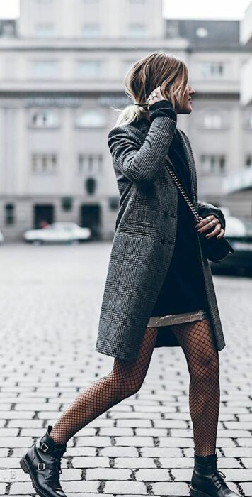 Girl wearing gray coat with black plaid, black turtleneck dress, fishnet stockings and black ankle boots