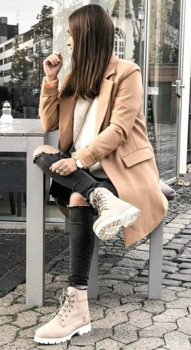 Girl wearing camel coat, beige sweater and ripped black jeans with camel booties