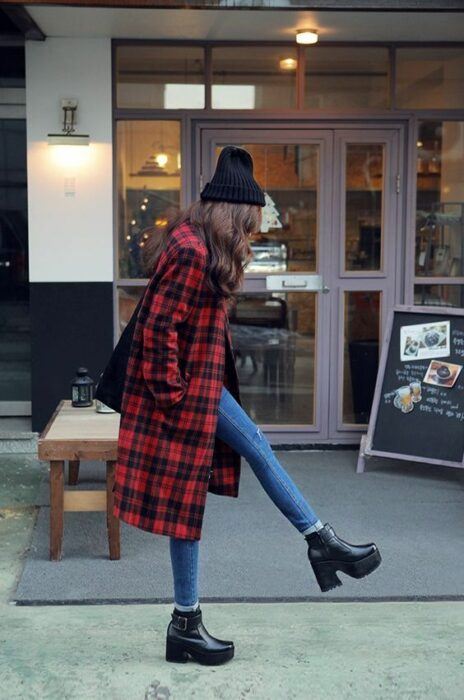 Chica usando gorrito color negro, con abrigo rojo con cuadros negros, jeans y botines de tacón color negro