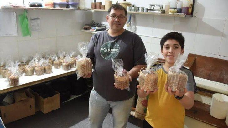 Padre e hijo dentro de la cocina sosteniendo pan de caja; Padre e hijo cocinan 400 panes para entregarlos a los más necesitados