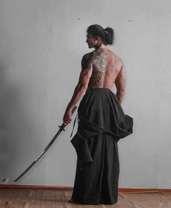 Paing Takhon con traje de samurái con pecho descubierto y un sable en la mano izquierda