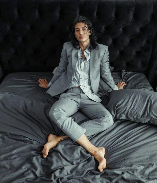 Paing Takhon sentado en una cama con sábanas grises