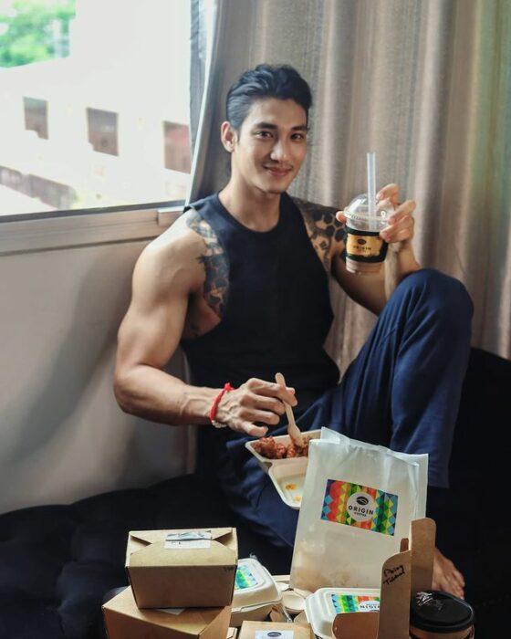Paing Takhon sentado comiendo con una playera negra sin mangas