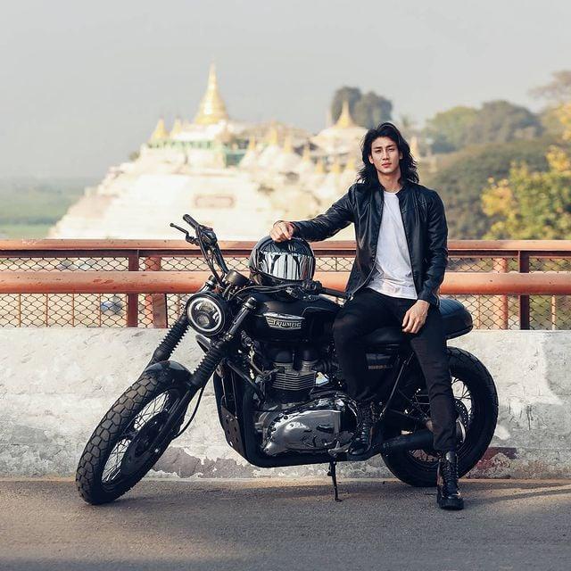 Paing Takhon posando en una motocicleta negra vistiendo un pantalón y chamarra negra con playera blanca